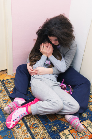 maltrato: Dos jóvenes hermanas llorando. Concepto: violencia doméstica y familiar. Abuso Infantil. Foto de archivo
