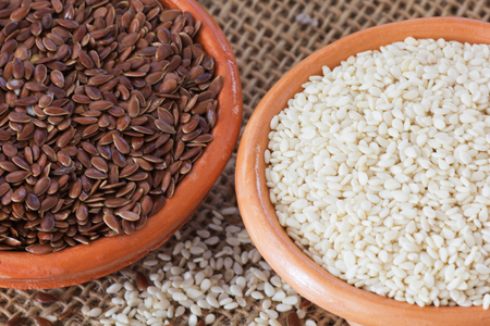 white sesame seeds: Bowls with Brown Flax Seed and White Sesame Seeds. Stock Photo