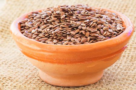organic flax seed: Organic and Raw Flax Seed in Bowl on Sack.