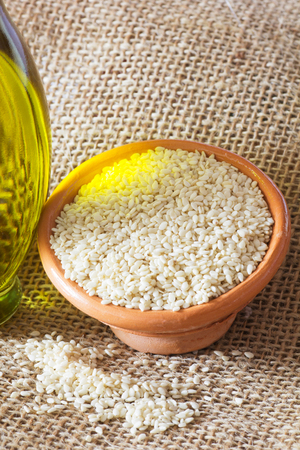 white sesame seeds: Bowls with Brown Flax Seed and White Sesame Seeds and Bottle of Oil.