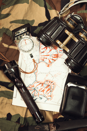 rescue west: Military Map and Compass on Military Camouflage Background. Image is Retro Filtered. Stock Photo