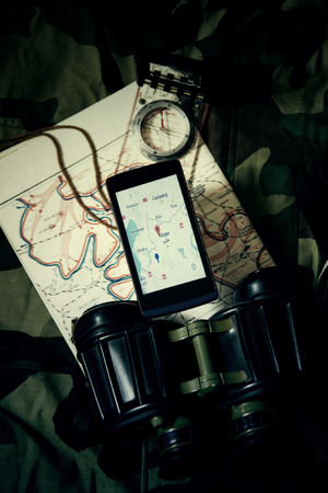 rescue west: Military Equipment and Mobile with a Map of Syria - Aleppo. Image is Retro Filtered.