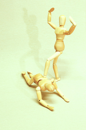 Wooden Dolls in Concept of Domination and Humiliation.  Image is Retro Filtered. Stock Photo