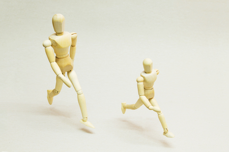 Wooden Dolls on Running Pose. Concept of Progress and Success.
