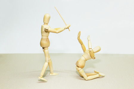 subjugation: Wooden Dolls in Concept of Aggression and Domination. Stock Photo