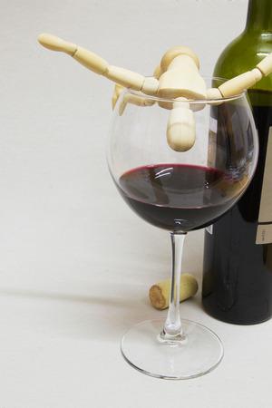 alcoholismo: La muñeca de madera y medio vacío copa de vino. Concepto alcoholismo.
