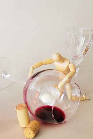 Drewniane lalki i Half Empty Glass of Wine. Alkoholizm Concept.