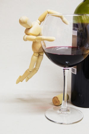 Wooden Doll and Half Empty Glass of Wine. Alcoholism Concept.