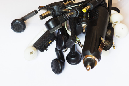 Many diferent old earphones and connectors on white background.