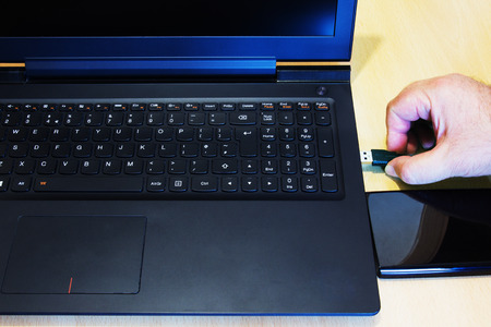 Hand connects a external hard drive to laptop computer by USB cable.