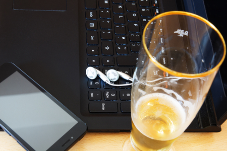 Glass of beer, laptop computer and smartphone on table. Stok Fotoğraf