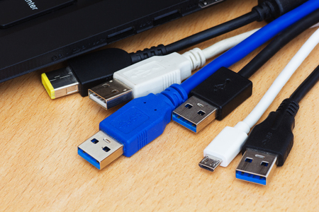 Many diferent usb cables and laptop on wooden background.