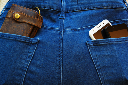 Two smartphones and a leather wallet in the back pockets of jeans. Reklamní fotografie
