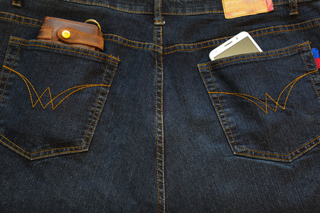 Cellphone and a leather wallet in the back pockets of jeans.