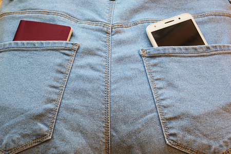 Passport with a smartphone in the back pocket of blue jeans. Imagens