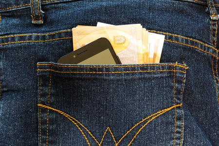 Euro banknotes and cellphone in the back pocket of blue jeans. Imagens