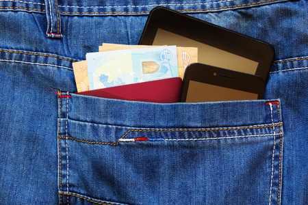 Passport and money with two smartphones in the back pocket of jeans.