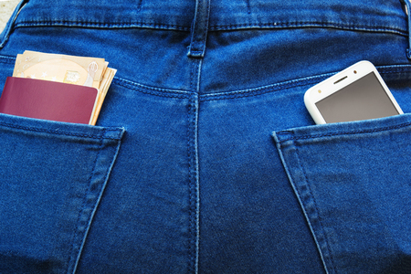 Passport and money with modern smartphone in the back pockets of jeans.