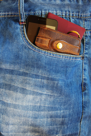 Passport and a leather wallet with modern smartphone in the pocket of old blue jeans. Reklamní fotografie
