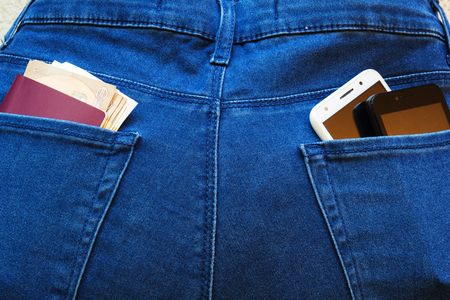 Passport and money with two smartphones in the back pockets of jeans. Stok Fotoğraf