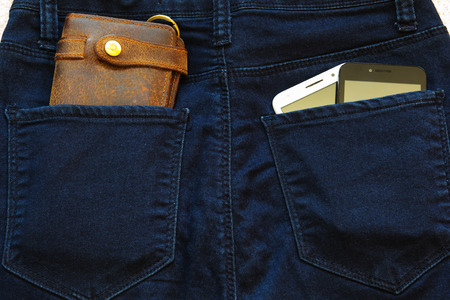 Two smartphones and a leather wallet in the back pockets of jeans. Banco de Imagens