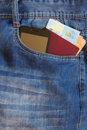 Passport and money with modern smartphone in the front pocket of old jeans.