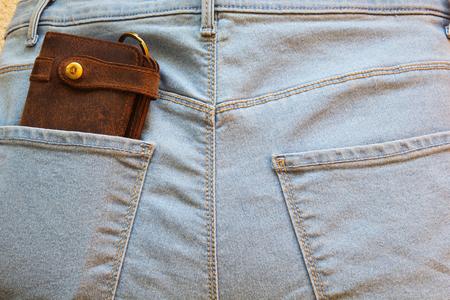 Brown leather wallet in the back pocket of blue jeans. Banco de Imagens