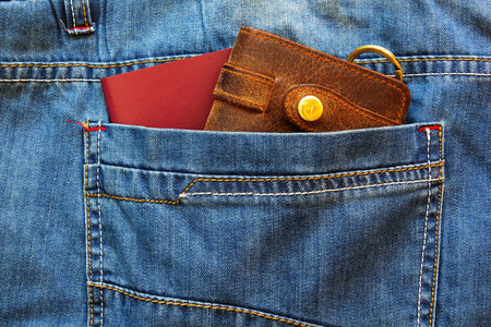 Passport with a leather wallet in the pocket of old blue jeans. Banco de Imagens