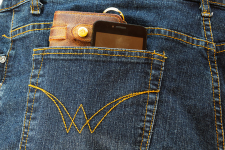 Cellphone and a leather wallet in the back pocket of blue jeans.
