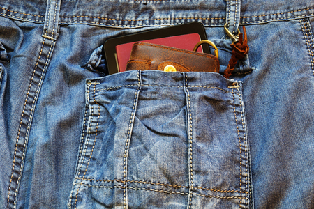 Passport and a leather wallet with modern smartphone in the pocket of old blue jeans. Banco de Imagens
