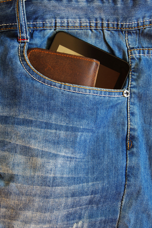 Cellphone and a leather wallet in the front pocket of old blue jeans.