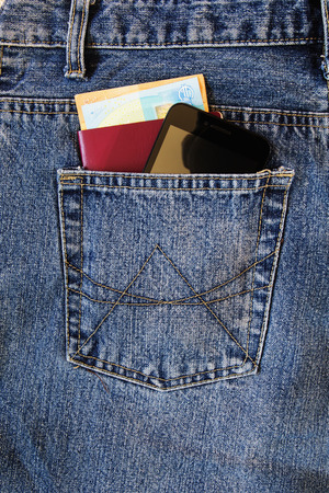 Passport and money with modern smartphone in the back pocket of jeans. Banco de Imagens