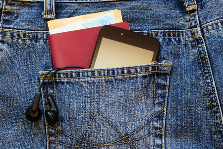 Passport and money with modern smartphone in the back pocket of jeans. Imagens