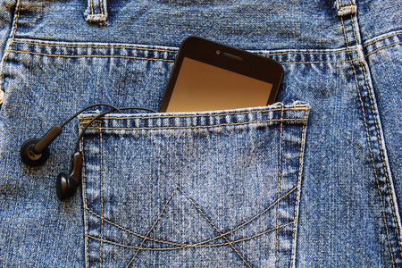Smartphone with a earphones in the back pocket of blue jeans.