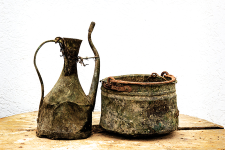 Ancient traditional household utensils over old traditional table from Macedonian village. Filtered. 스톡 콘텐츠