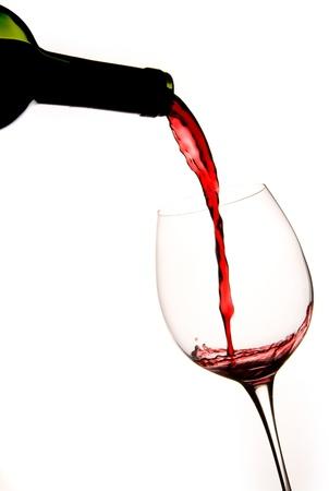 Versando un bicchiere di vino rosso con sfondo bianco