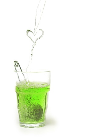 Pouring a heart of green tea into a glass photo