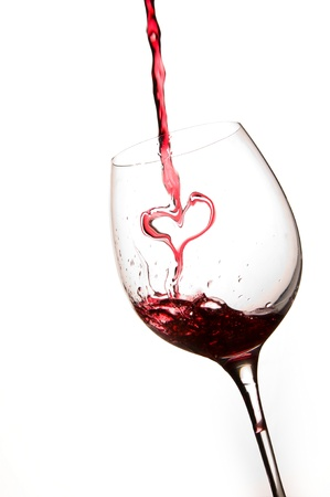 Pouring a heart of red wine in a glass white background Standard-Bild