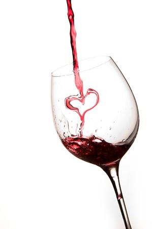 bodegas: Verter un coraz�n de vino tinto en un fondo de vidrio blanco