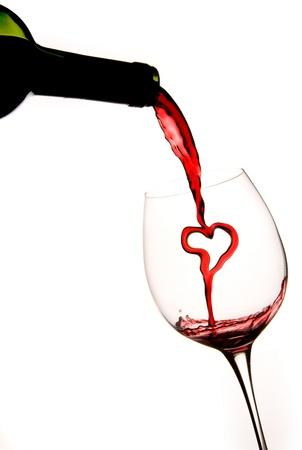 Gieten van een hart van rode wijn uit een fles