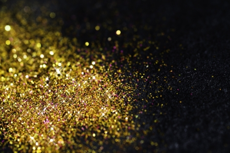 Gold glitter on black background with selective focus