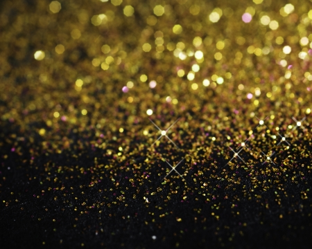 Gold glitter on black background with selective focus photo