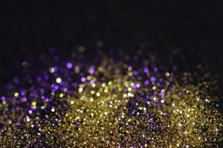 Goud en paars glitter op zwarte achtergrond met selectieve focus