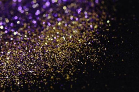 sparkles: Gold and purple glitter on black background with selective focus Stock Photo