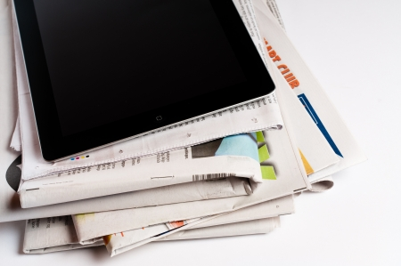 A stack of newspapers with an iPad 3 on the top