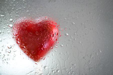 corazon roto: Coraz�n rojo detr�s de un vidrio mojado. Amor triste, coraz�n roto.