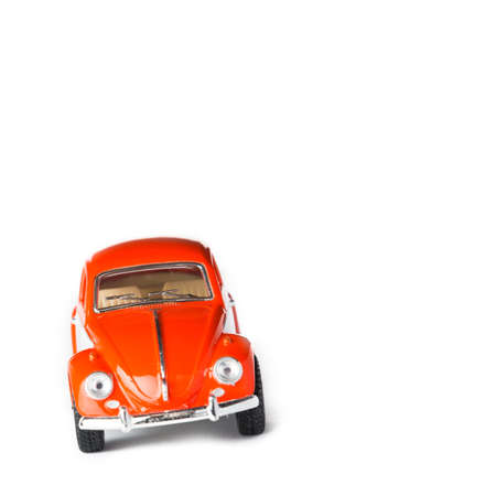 car front view: An orange VW toy car front view. Also known as beetle.