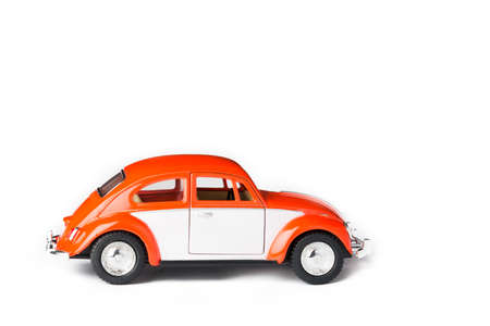 man made object: An orange VW toy car. Also known as beetle.