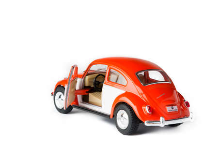 man made object: An orange VW toy car with the door open. Also known as beetle.