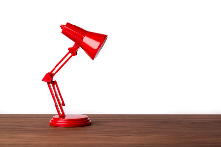 desk lamp: Red metal lamp on a wooden desk shining on the table. Light steam.